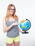 Happy young girl pointing finger on world globe Stock Images