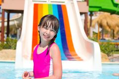 Happy young girl in pool. Happy young girl in swimming pool with colorful slide in background Royalty Free Stock Images