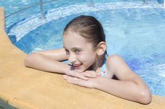 Happy young girl in pool. With hands on chin Royalty Free Stock Image