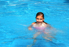 Happy young girl in a pool. A cute, happy and smiling girl in a blue pool by a sunny summer day Stock Photography