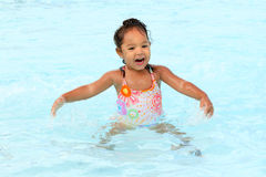 Happy young girl in a pool. Young girl splashes in the pool Royalty Free Stock Photography
