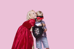 Happy young girl in princess costume hugging boy pretending to be her hero over pink background Royalty Free Stock Photography