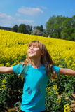 Happy young girl in rape field Stock Images