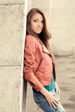 Happy young girl in red jacket. Beautiful Girl in Red Jacket standing near wall royalty free stock photography