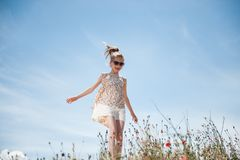 Happy young girl refreshed by the wind walking among field of flowers on blue sky background. Happy caucasian little girl refreshed by the wind walking among Stock Photography