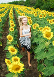 Happy young girl running in the field. Of sunflowers Royalty Free Stock Images