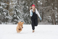 Happy young girl running in the snow with her golden retriever d Royalty Free Stock Photo