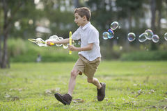 Young boy running with bubble wand Stock Photography