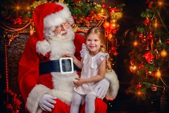 Merry christmas from santa. A happy young girl is with Santa Claus at home. Merry Christmas and Happy New Year royalty free stock photography