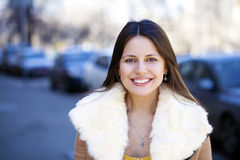 Happy young girl in sheepskin coat on a background of the city Royalty Free Stock Image