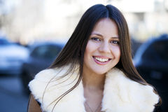 Happy young girl in sheepskin coat on a background of the city Royalty Free Stock Photo