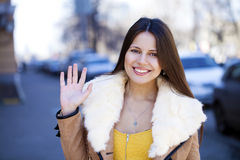 Happy young girl in sheepskin coat on a background of the city Royalty Free Stock Photography