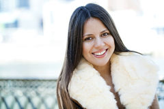 Happy young girl in sheepskin coat on a background of the city Stock Photos