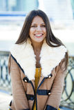Happy young girl in sheepskin coat on a background of the city Stock Photo