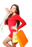 Happy young girl with shopping bags and a bouquet of gerbers on Stock Photo