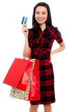 Happy young girl with shopping bags and credit card Royalty Free Stock Photos
