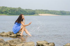 Happy young girl sitting on the bank of river enjoying condition comes summer Royalty Free Stock Photo