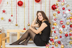 Happy young girl sitting on a bench in a New Years interior Stock Photos