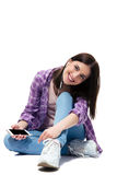 Happy young girl sitting on the floor with smartphone Stock Photo