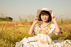 Happy young girl sitting in a flowery meadow in summertime. Royalty Free Stock Photo