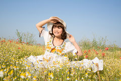 Happy young girl sitting in a flowery meadow in summertime. Royalty Free Stock Image
