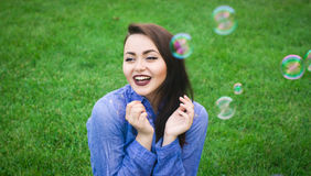 Happy young girl sitting on green grass. With soap bubbles Stock Photos