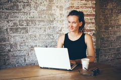 Happy young girl is sitting in a loft cafe and chatting with her boyfriend using laptop Stock Photography