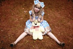 Happy young girl sitting on meadow with teddy bear in summertime dressed as doll Royalty Free Stock Photography