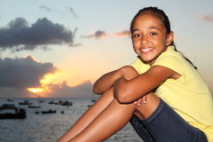 Happy young girl sitting by seaside at sunset Stock Image