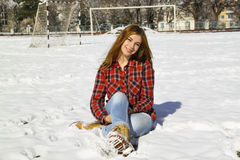 Happy young girl sitting on the snow in the park Stock Photography