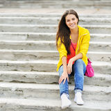 Happy young girl sitting on the stairs and smiling Stock Photo