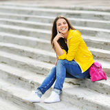 Happy young girl sitting on the stairs and smiling Stock Photos