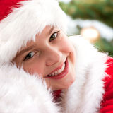 Happy young girl smiling  near the Christmas tree. Stock Photography