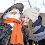 Happy young girl with a snowman, close up Stock Image