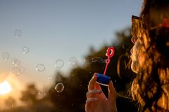Happy young girl with soap bubbles in autumn at sunset royalty free stock photo