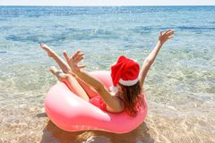 Happy Young girl with Santa Claus hat in a sprinkled donut float in the sea, smiling with sunglasses for summer. Happy Young girl in a sprinkled donut float in royalty free stock image