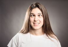 Happy young girl squinting. On a gray background Stock Photos