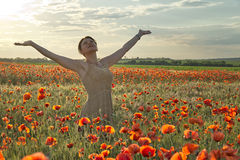 Happy young girl standing in the poppies field Royalty Free Stock Images