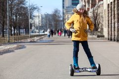 Happy young girl standing on self balanced vehicle on street pathway, copy space Stock Images