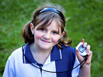 Happy young girl with stop watch at sports day. Young girl pleased with her efforts after checking stop watch at school sports day Royalty Free Stock Photography