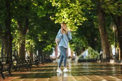 Happy young girl student with backpack. Holding mobile phone, walking at the park Royalty Free Stock Photography