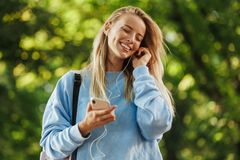 Happy young girl student with backpack. Holding mobile phone, walking at the park, listening to music with earphones Royalty Free Stock Photo