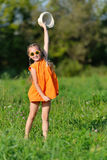 Happy young girl in sun glasses jumping playing on a meadow in sunny day Royalty Free Stock Images