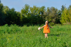 Happy young girl in sun glasses jumping playing on a meadow in sunny day Royalty Free Stock Photo