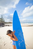 Happy young girl with surfboard at beach Stock Photo