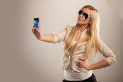 Happy young girl taking pictures of herself. Stock Photo