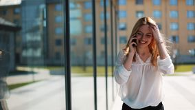 Happy young girl talking on the smartphone, walking down the street near the office center. Woman dressed in business. Clothes Summer time. The concept of stock video footage
