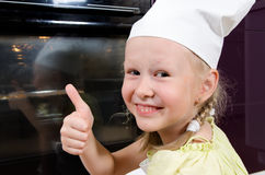 Happy young girl in a toque giving a thumbs up Royalty Free Stock Photos