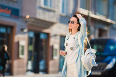 Happy young girl tourist in european city. Caucasian woman walking along the old streets of Europe. Girl caucasian drinking hot drink coffee walking in street at Stock Photo