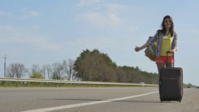 Happy young girl traveling hitchhiking. Young smiling girl with backpack behind her back and suitcase in hand stands near the highway and waits when the stock footage